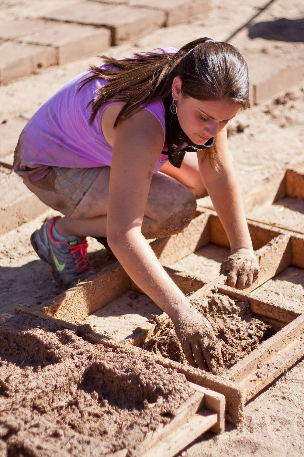 Volunteer filling a brick form.
