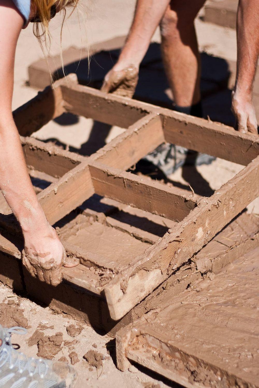 Volunteers pulling an adobe brick form.