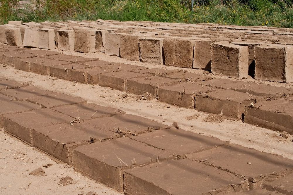 Volunteer bricks in the field at an owner builder support project.