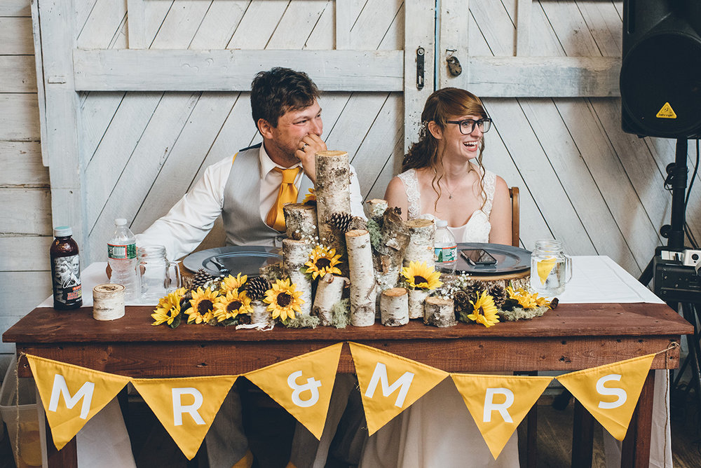 Sunflower and birch tree sweetheart table. Mountain and forest DIY wedding.