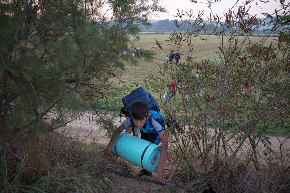 A Syrian boy scrambles up a path near the Macedonian border. Dan Kitwood/Getty