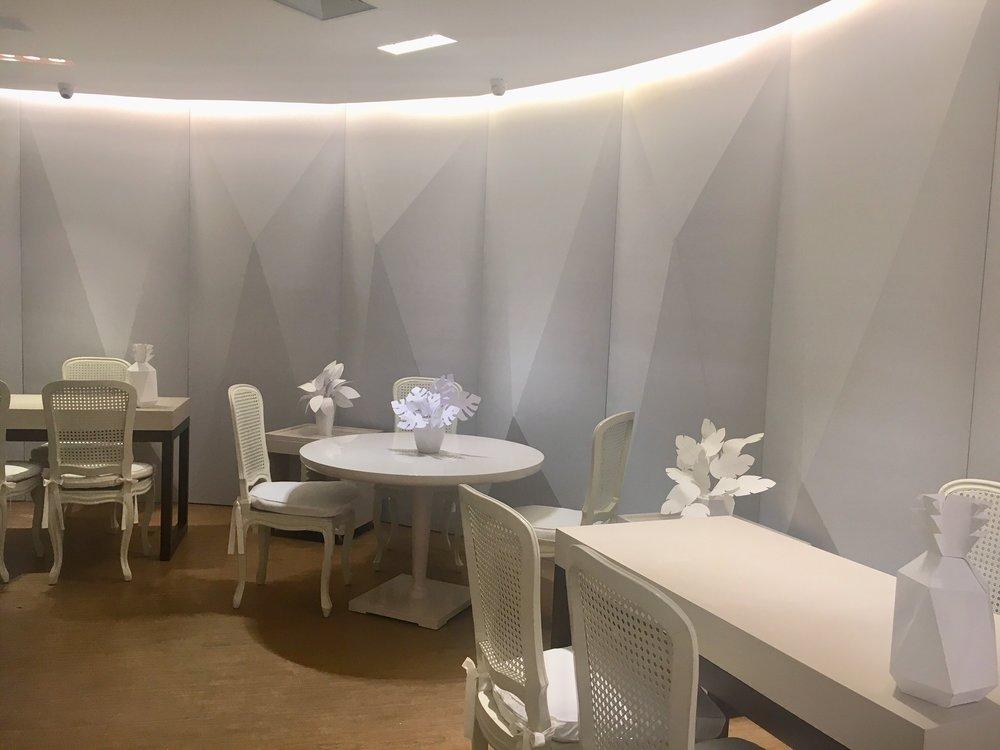 Nove metros de parede curva com fechamento geométrico e mobiliário todo branco. Representação da frieza e rigidez da época, usada como pano de fundo construído para ressaltar o colorido das jóias e a exuberância da personalidade de Carmem Miranda.