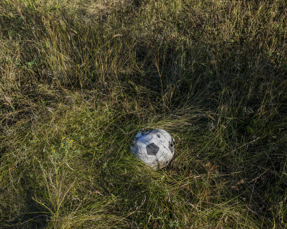 """A soccer ball punctured by shrapnel in the village of Pisky.  """"Everybody wants to stop this war, everybody wants peace."""" -Giorgiy, 68, Anatol"""
