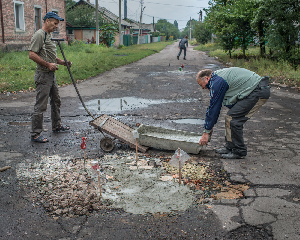 """We repaired this pothole a year ago, now we're repairing it again. Prices are going higher and it's very hard for young people to find work. I worked in the coal mine before I retired. This town was built around coal mines, but when the war started a lot of people left. Nobody knows if the ceasefire will last but I hope the shelling will stop."" -Victor, 62, Novoradivke."