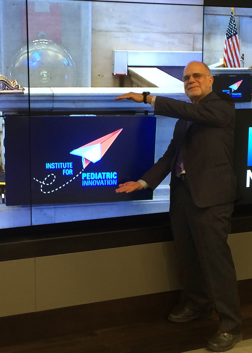 Founder Don Lombardi poses with IPI's logo at the New York Stock Exchange before ringing the closing bell in August of 2016.