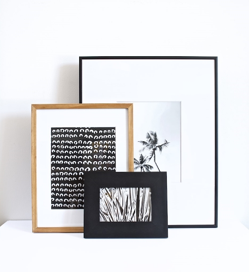 Our black and white prints stacked on a shelf