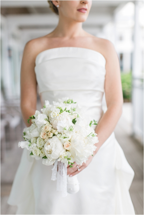 White structured wedding gown with white bouquet photographed by Deborah Zoe Photography.