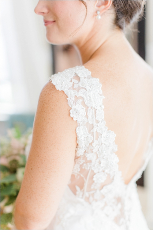 Delicate lace detailing on wedding dress photographed by Deborah Zoe Photography.