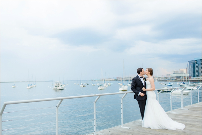 Couple embrace during rainstorm for Boston Aquarium wedding photographed by Deborah Zoe Photography.