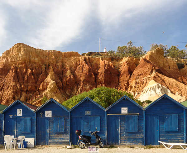 blue painted huts and rock face portugal