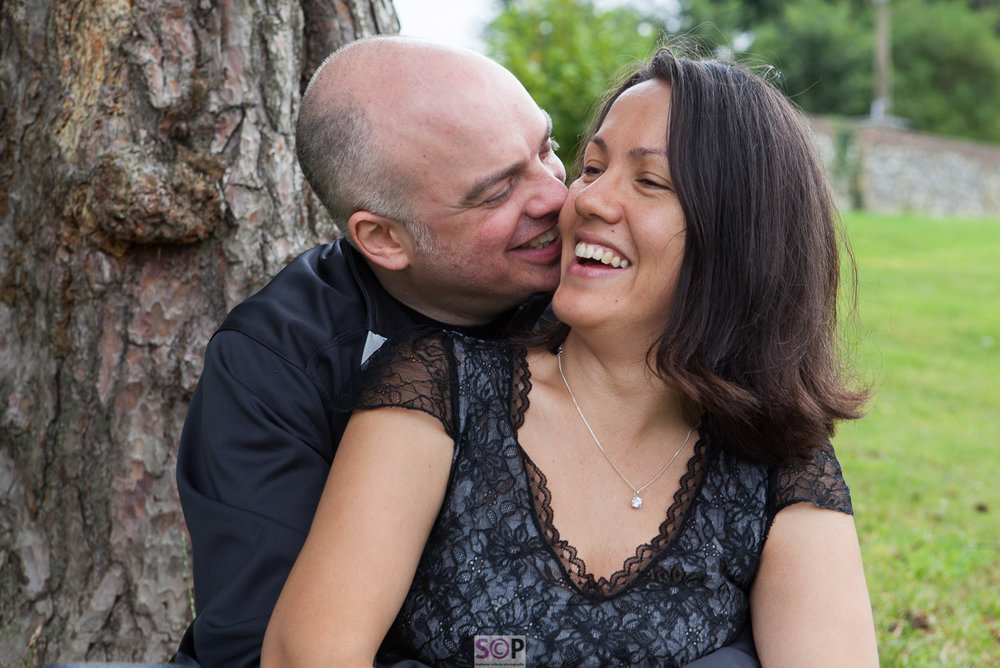 kiss on the cheek engagement shoot image with couple laughing