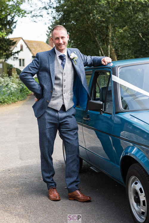 groom in blue suit leaning on vintage VW Golf