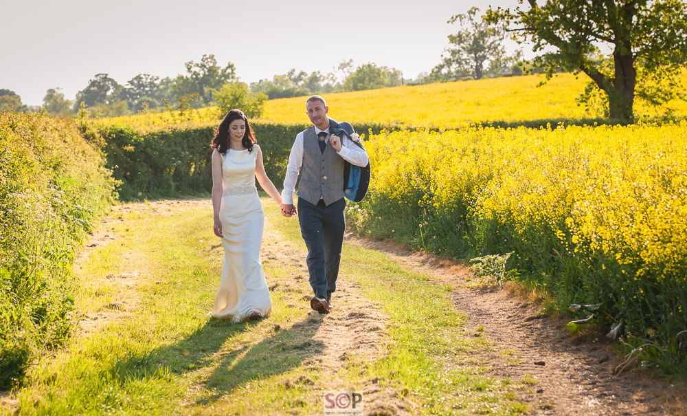 bride and groom walking by rapeseed field at onley farm rugby