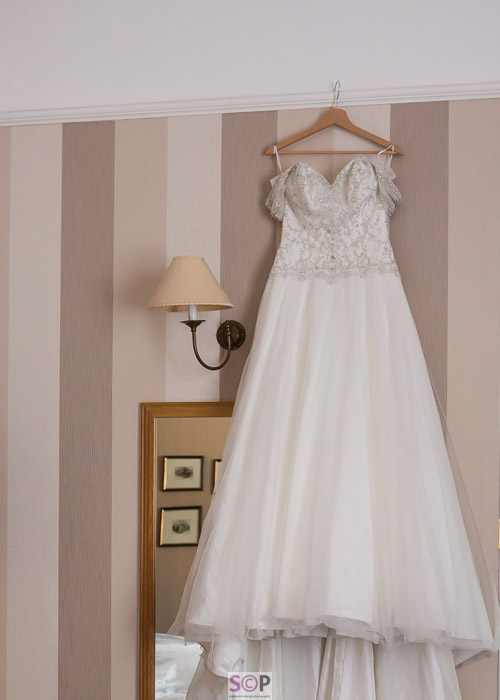 beaded wedding dress hanging on coat hanger