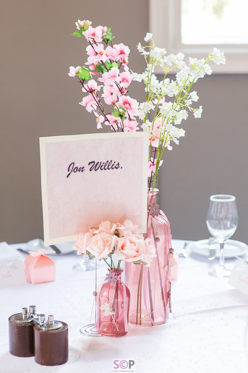 pink and white flowers on white cloth table setting