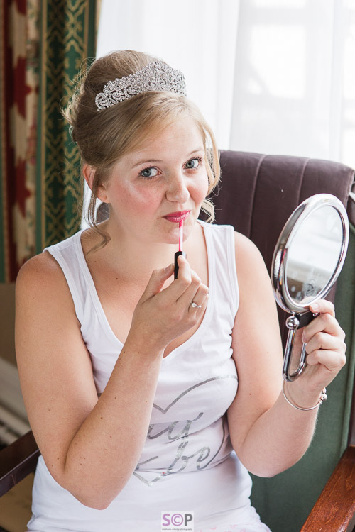 bride sitting with mirror applying lipgloss
