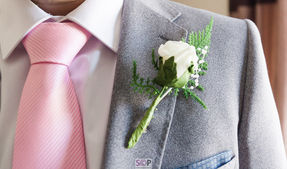 close up of grooms grey suit pink tie and white rose button hole