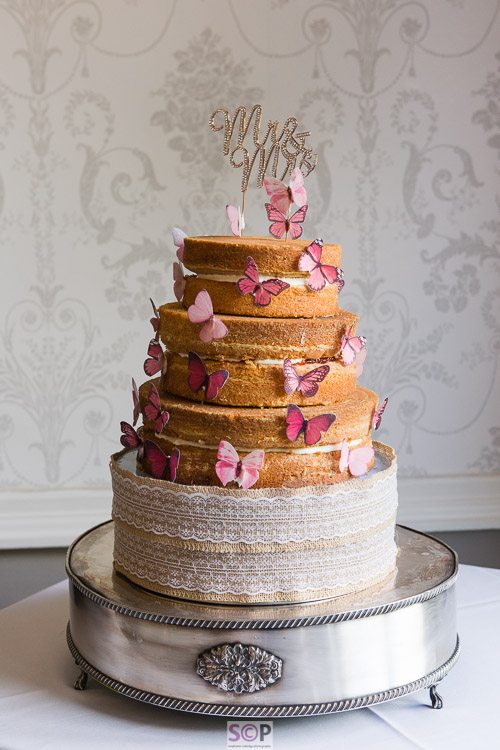 naked wedding cake with pink butterflies