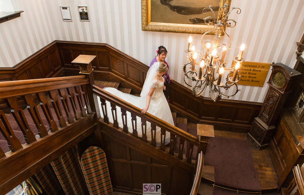 bride and brides mum descend feature wooden stairs with chandelier