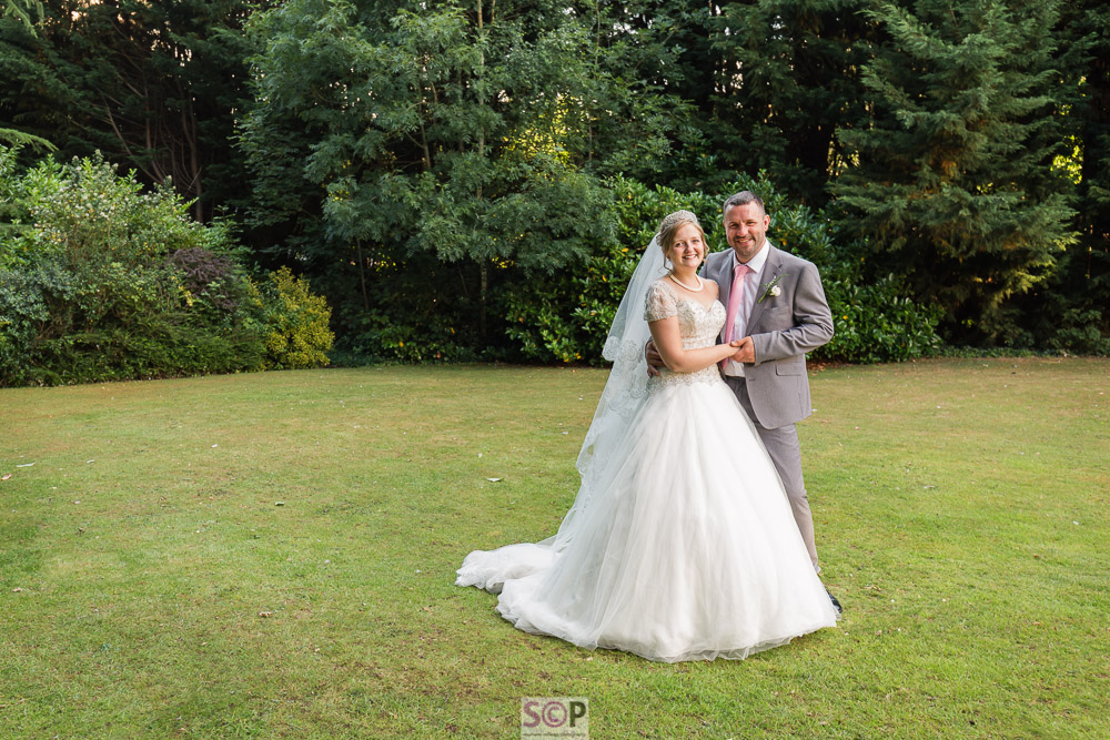 bride and groom on lawns at the chace hotel coventry full length image