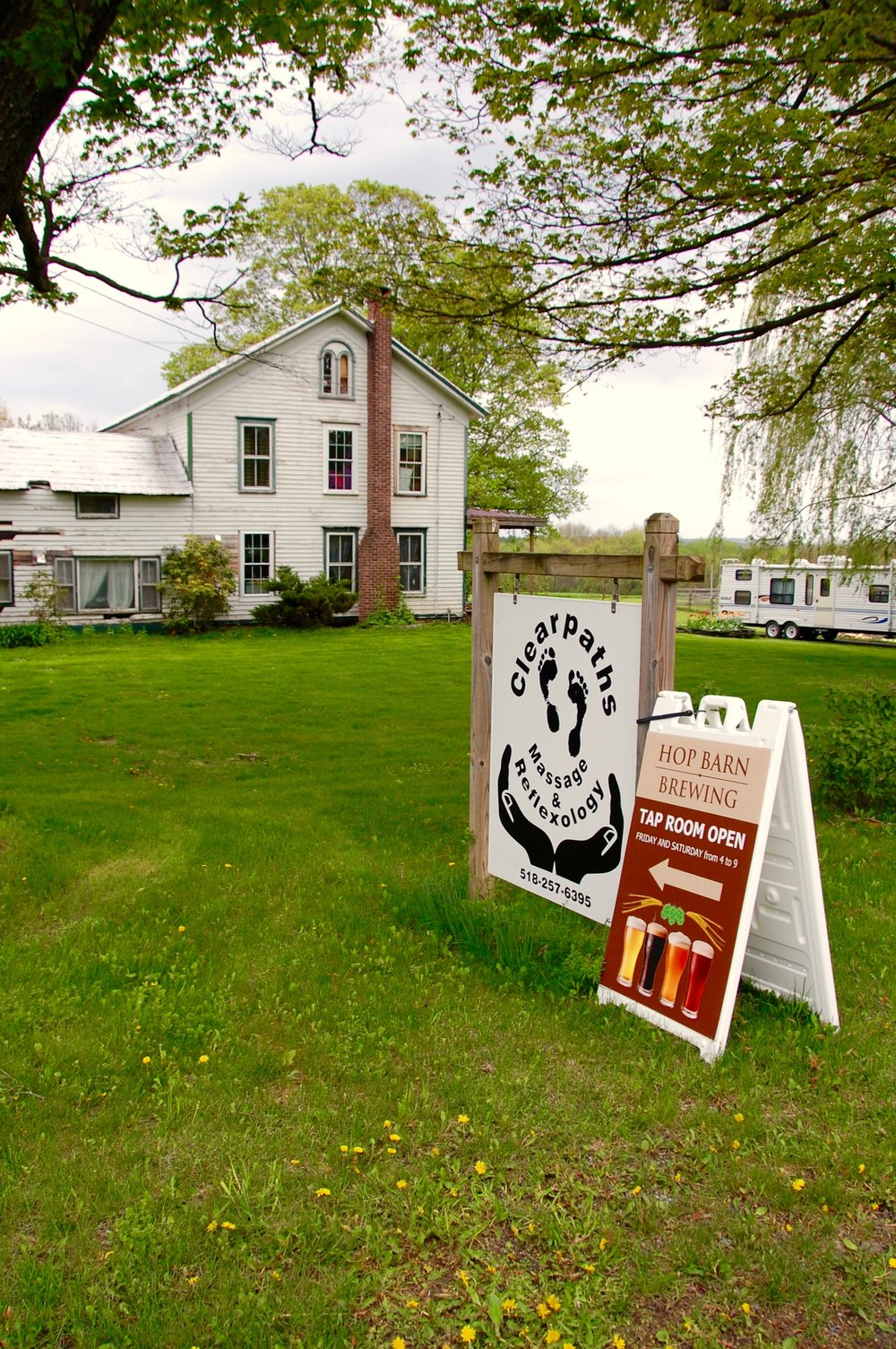 Hop Barn's front lawn, with side-by-side signage for another in-home business, Clear Paths Massage and Reflexology.