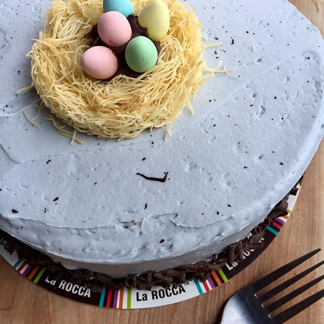 "Chocolate Mini Egg Cake - Our popular Chocolate Fudge cake enrobed in ""robins egg"" blue frosting, with chocolate speckles, topped with a phyllo pastry nest with Cadbury mini eggs #easter"