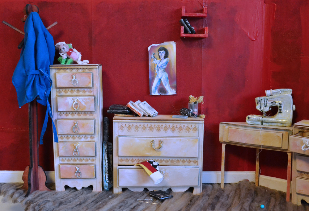 Miniature books and red plastic shelves are laser-cut.  Miniature  sewing machine is resin and found object made.  Clothing is hand sewn.  Flowers are hand made using dried flower petals.