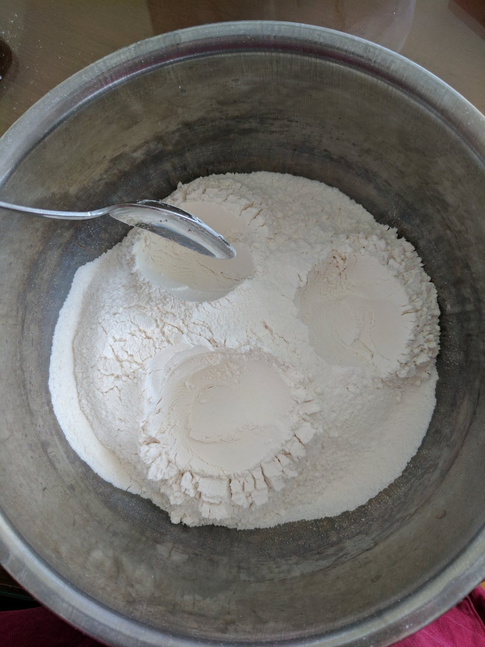 1. Place sifted flour in a mixing bowl. Use back of a spoon to dug three holes