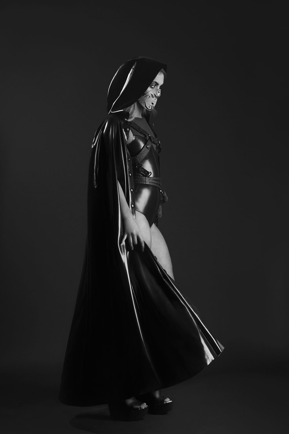 Tohunga mask:  Christina Ioannidou ; Latex cape:  Atsuko Kudo ; Latex silhouette body:  Kim West ; Harness:  Ashley Isham ; Ascension sandals:  Gareth Pugh x Melissa