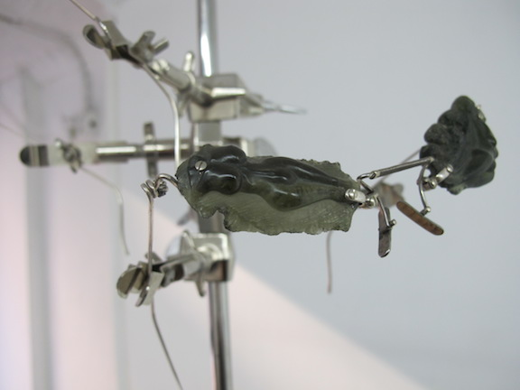 Elaine Cameron-Weir,  a terrestrial sediment melted by hypervelocity impacts from outer space, most fell on Bohemia, molten, forming strange shapes and solidifying bottle green like the eyes of a gorgon  (detail), 2014, stainless steel, sterling silver, laboratory clamps, carved moldovite, dimensions variable