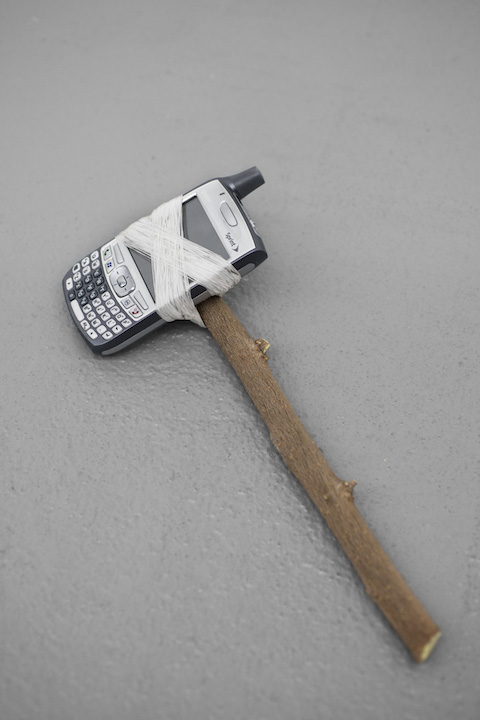 Bea Fremderman,  Weapon No. 1 (cellphone),  2017, Found cellphone, dental floss, branch, 11 x 4 in