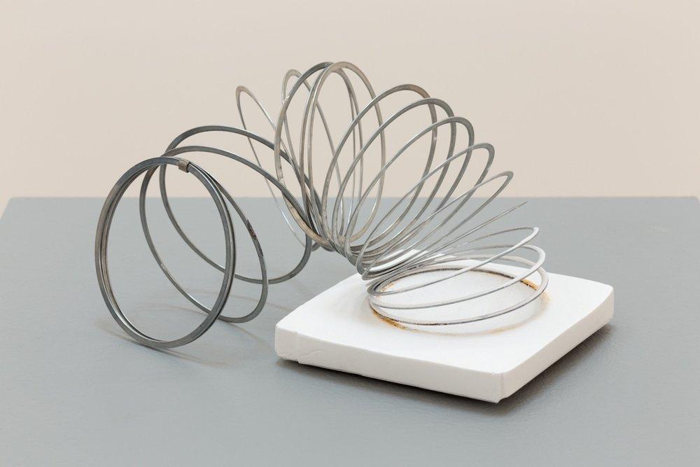 Deborah Hede,  Slinky , 2014, metal slinky, plaster, 4 × 7 × 4 in