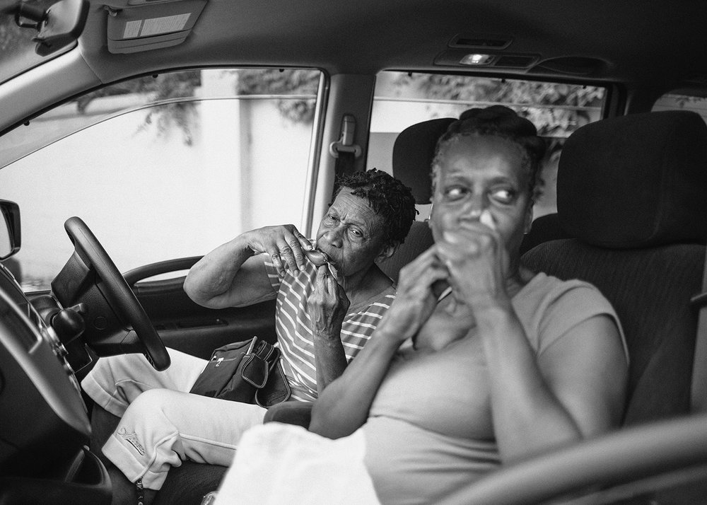 Sasha Phyars-Burgess,  Tanty Yoland and Aunty Arlene eating Mangoes, Crown Point, Tobago (SEA FULL) , 2018, black and white print on paper, 58 × 81 ½ in.