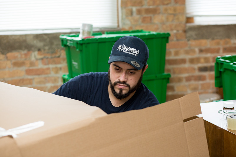 Green Moving Boxes behind The Professional Moving Specialists employee