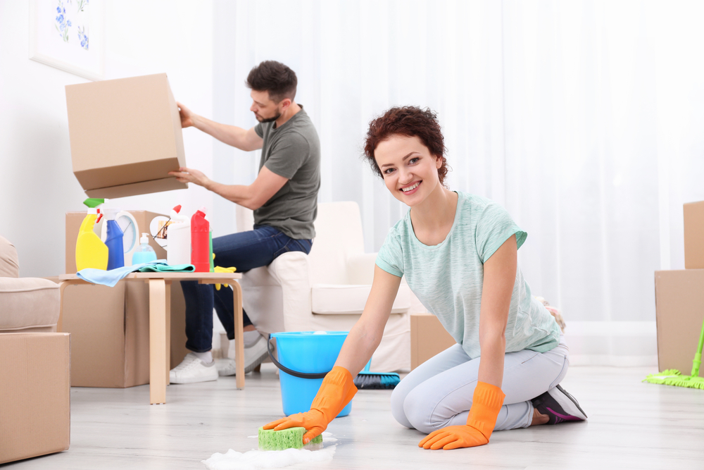 young happy couple cleaning their new house during a move