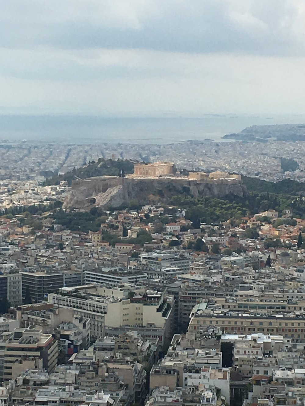 Acropolis rising above the city with the Aegean Sea in the back on a rare cloudy day