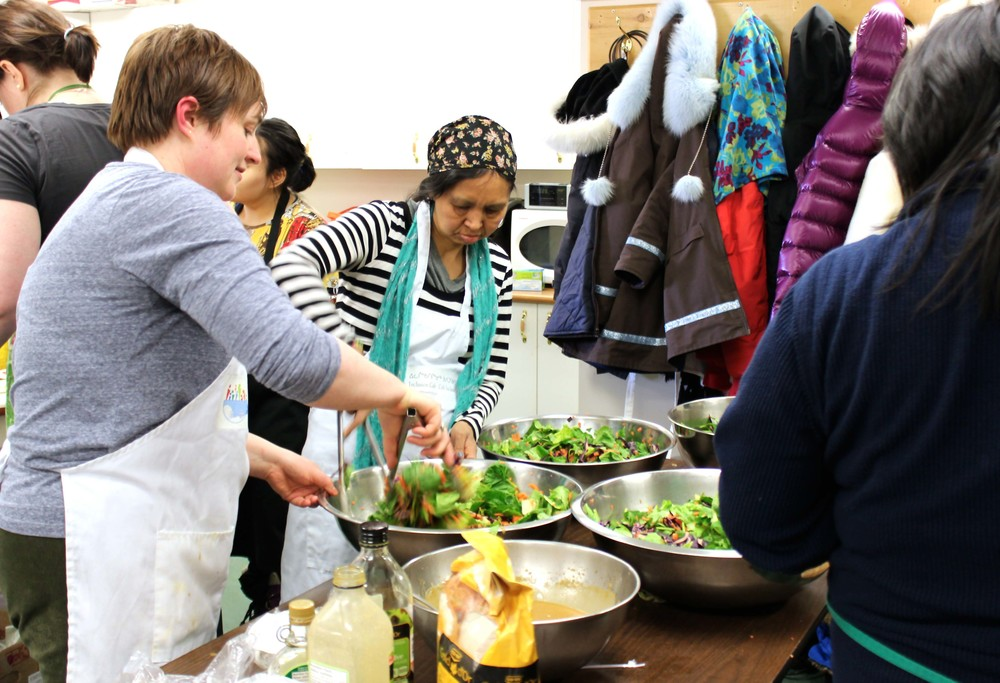 Inclusion Café's volunteers and staff busily prepare a healthy salad for dinner. Photo by Sarah Brandvold.