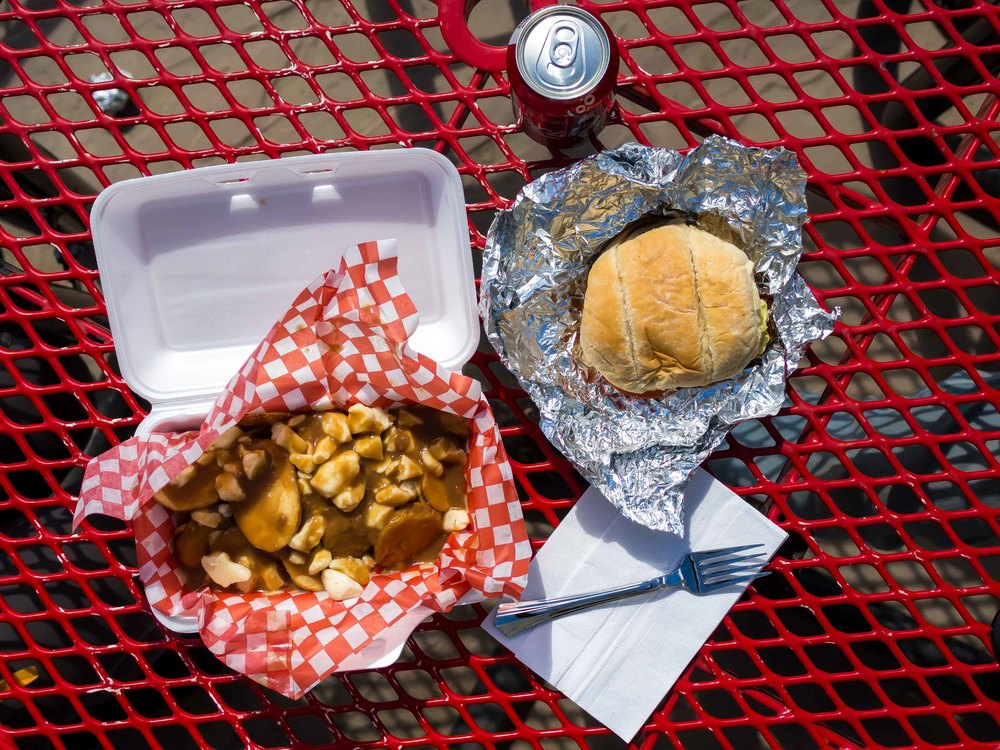 Lunch spread from Curbside Grill: burger, poutine, and a Coke.