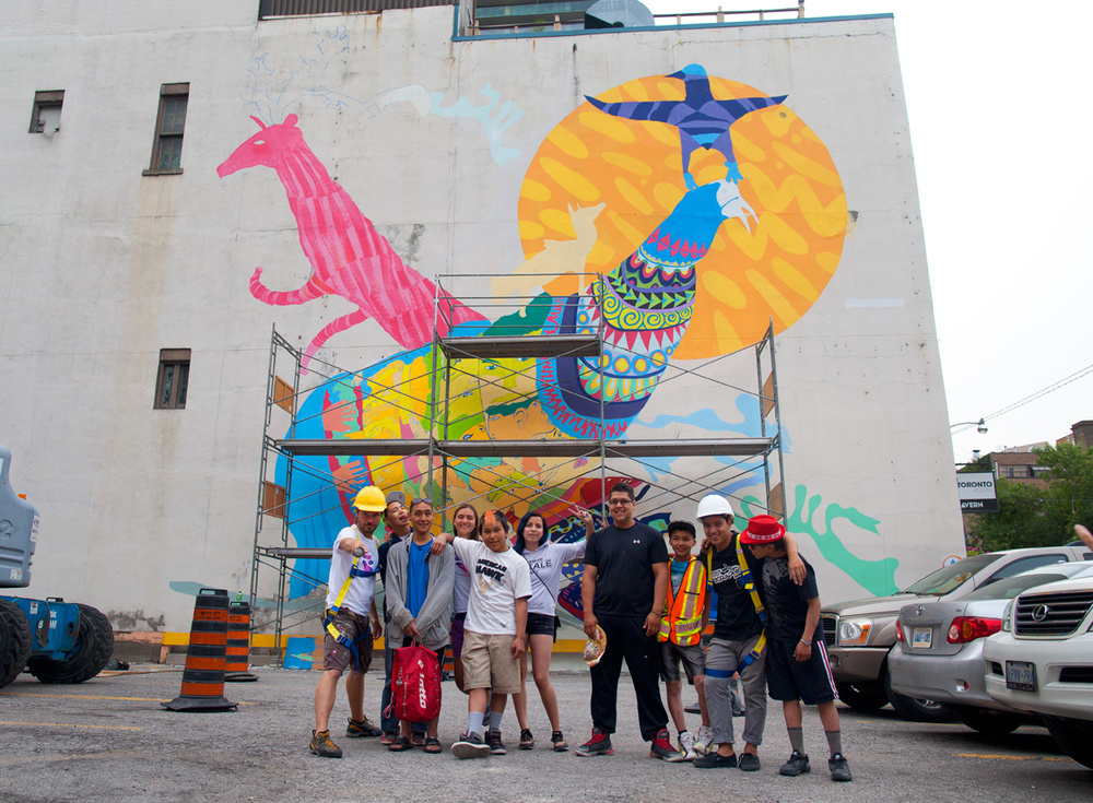 The Cape Dorset artists with the rest of the team in front of a partially-finished mural. Photo by Tobin Grimshaw.