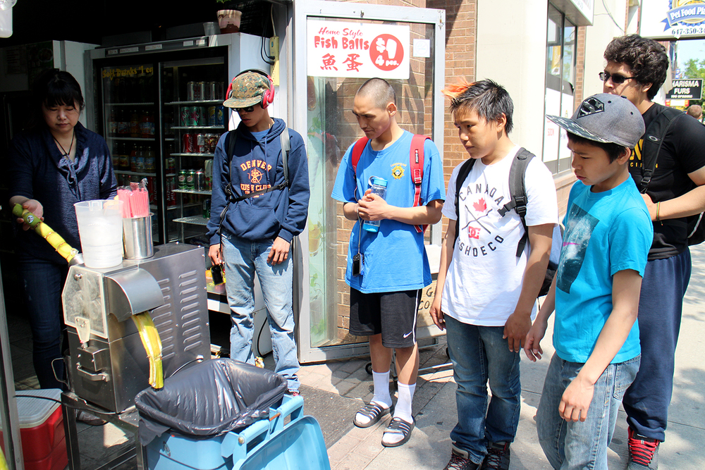 The boys try sugarcane juice in Chinatown. Photo by Alexa Hatanaka.