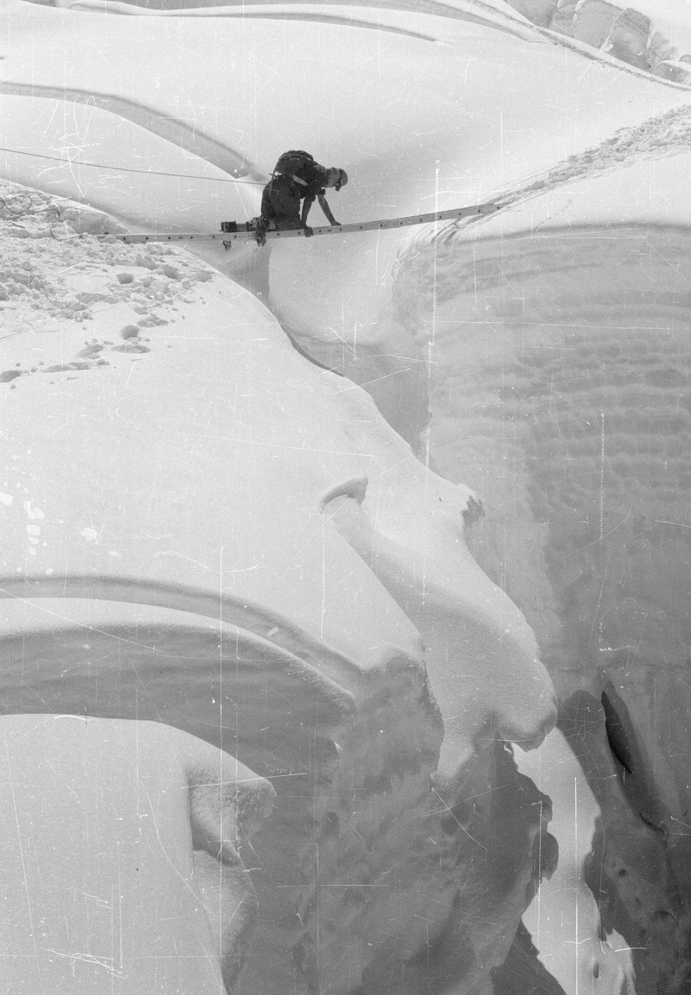 Edmund Hillary crossing a ladder bridge over a crevasse above Camp III in the Western Cwm during the reconnaissance. April 25th 1953. Photograph courtesy of The Royal Geographic Society (with IBG).