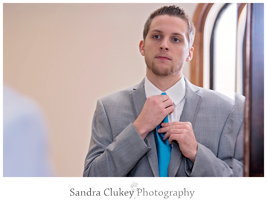 Groom fixes blue tie