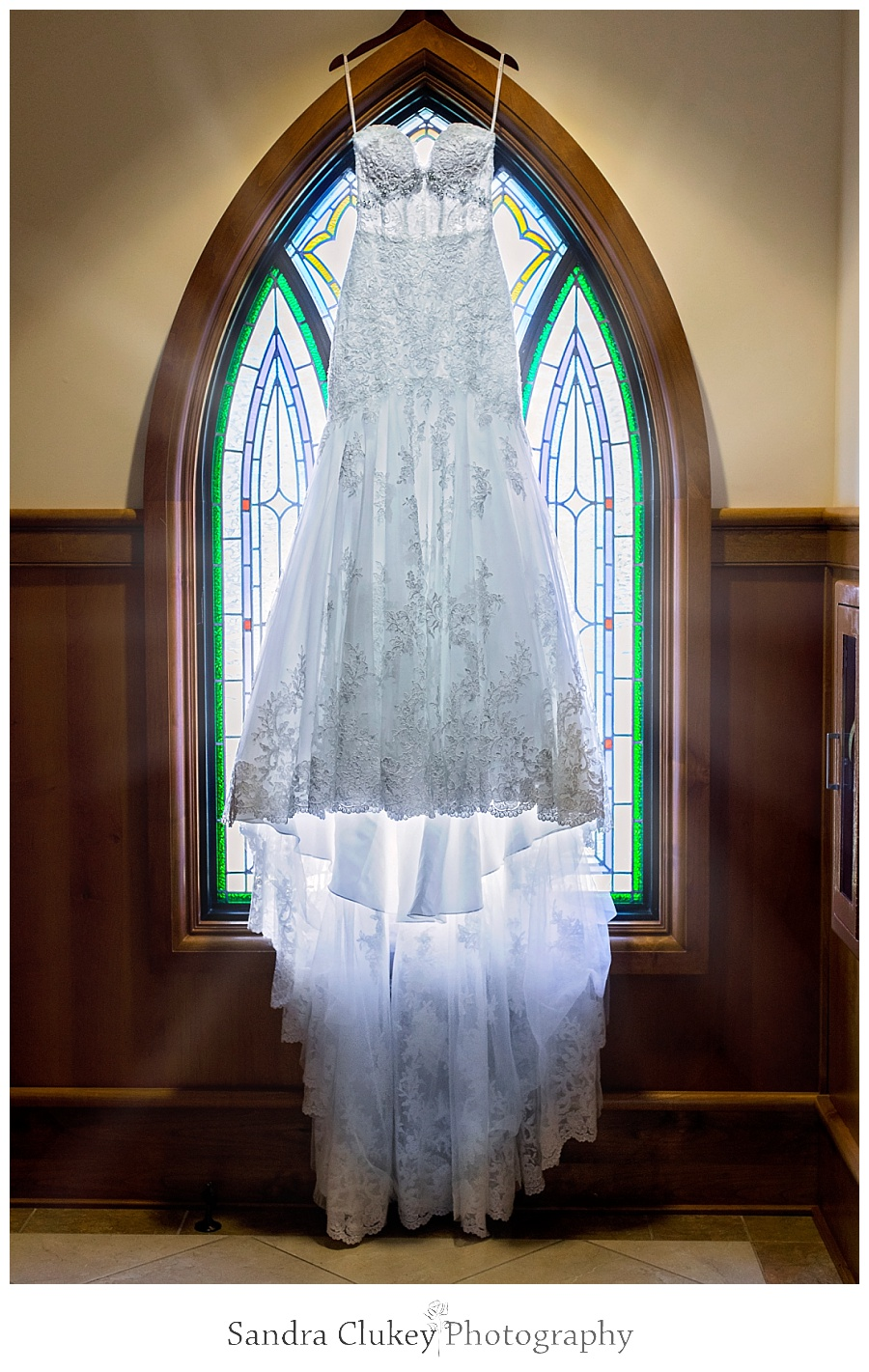 Gorgeous wedding gown by stained glass window