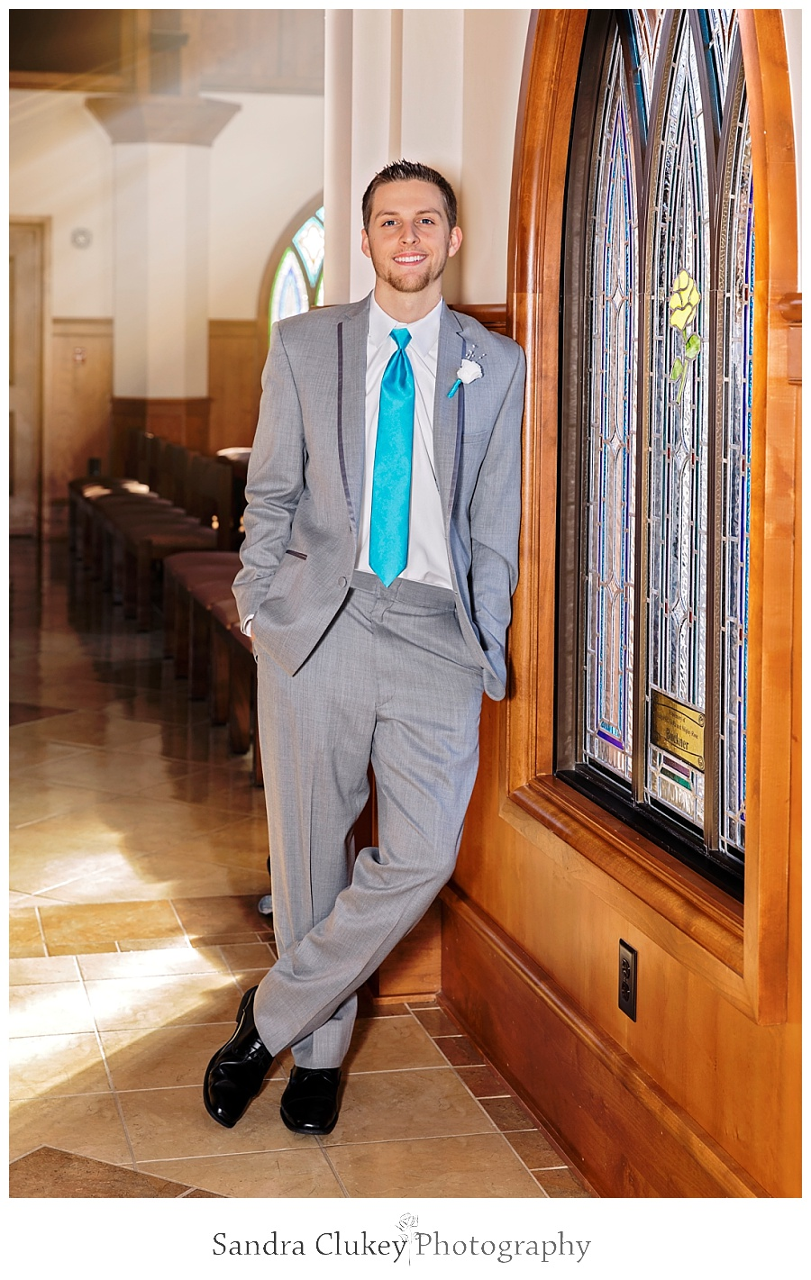Groom by stained glass chapel windows