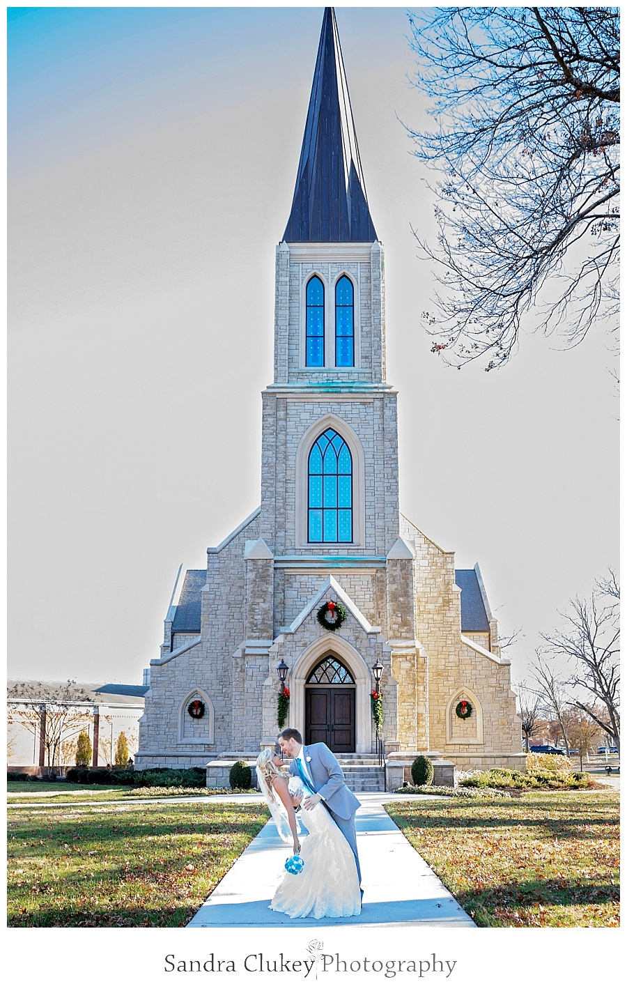 Groom dips bride in front of Chapel