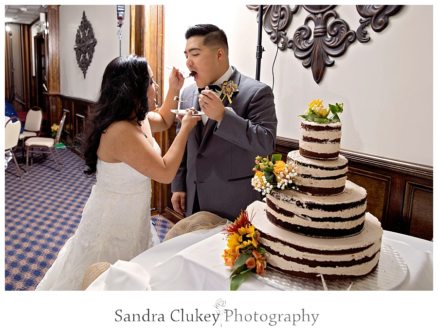 Wedding couple serve each other cake