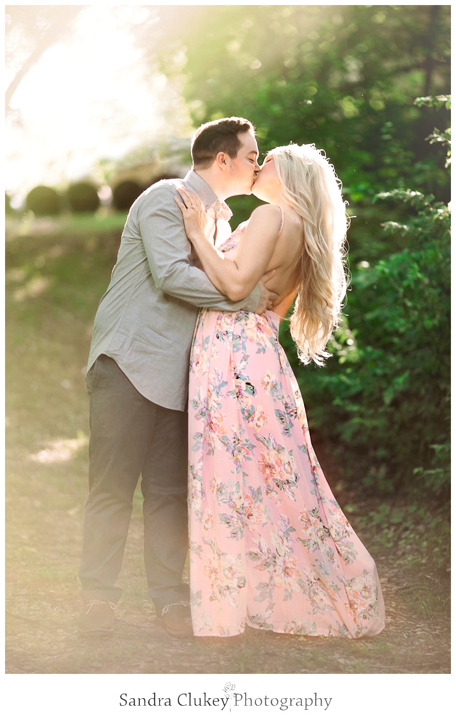 Whimsical couple kissing at sunset