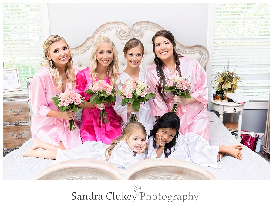 Bride on bed with bridesmaids
