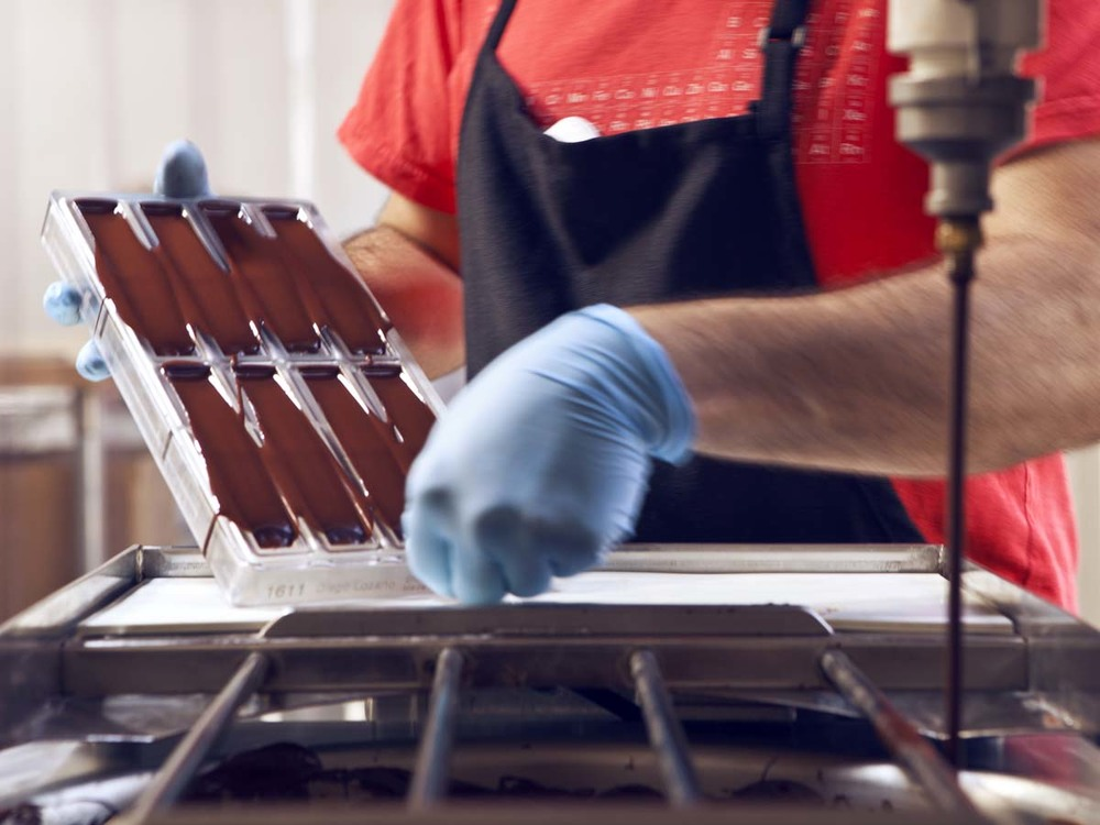 Dispensed chocolate is distributed evenly in the molds with a vibrating table.