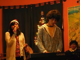 Fabiola sings as Fernando plays the piano at the Christmas party 2013.